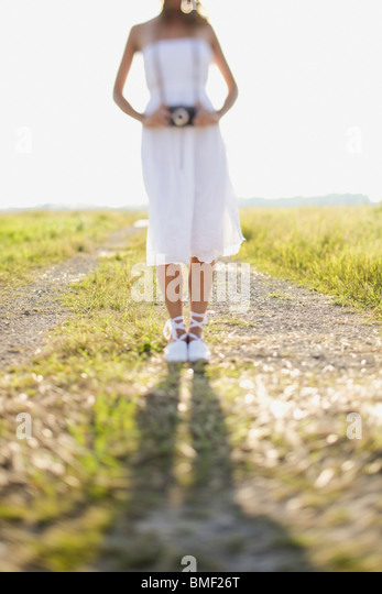 A Bride Standing On A Dirt Road In A Field With A Camera Around Her Neck - Stock Image