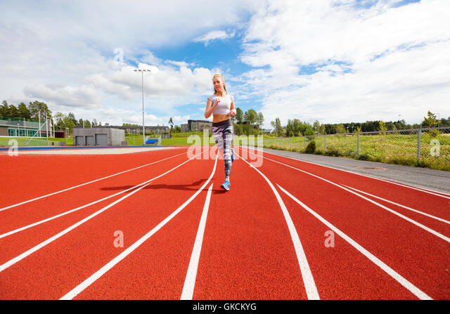 Fast athletic female runner on outdoor running track - Stock Image