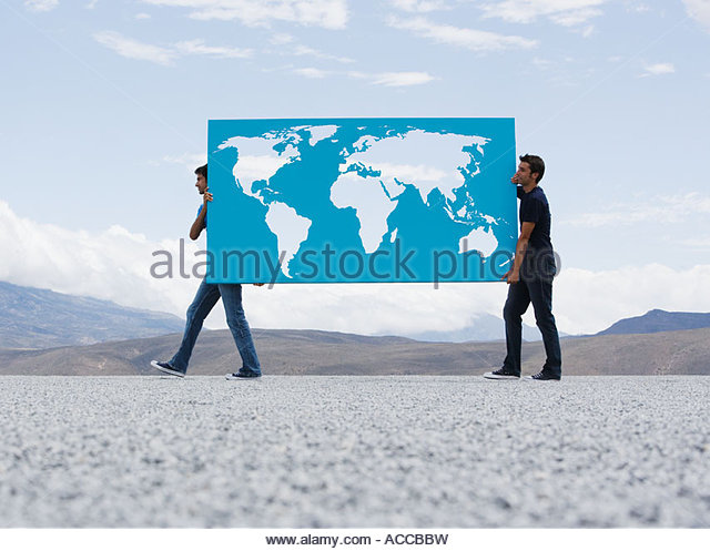 Two men carrying world map outdoors - Stock Image