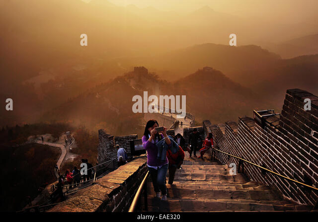 The Great Wall of China rises at sunset above the surrounding landscape overcast by smog at Badaling, some 70kilometers - Stock-Bilder