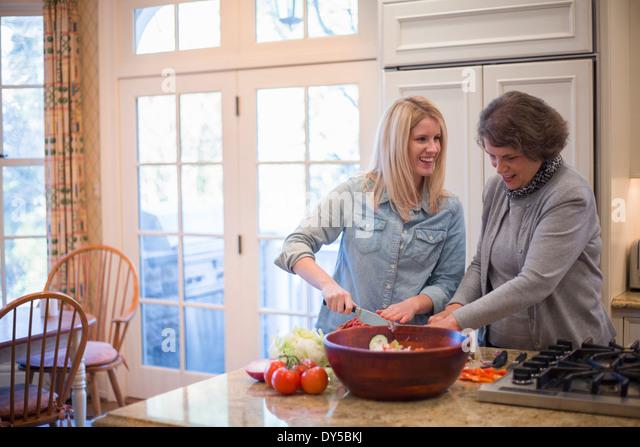 Senior woman and granddaughter preparing salad - Stock Image