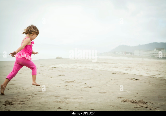 Female toddler running on beach - Stock Image