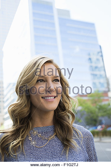 Close up portrait smiling businesswoman below city highrise - Stock Image
