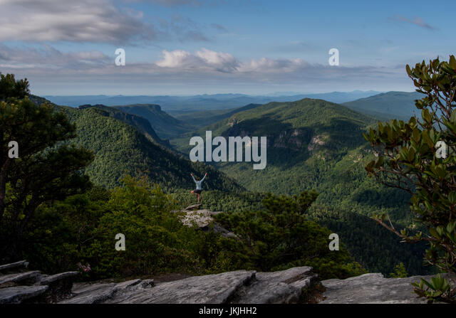 Woman Standing on One Leg Power Posing over Linville Gorge Wilderness - Stock Image