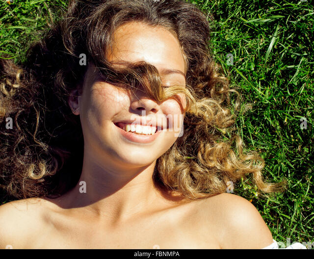 young cute summer girl on green grass outside relaxing smiling close up - Stock Image