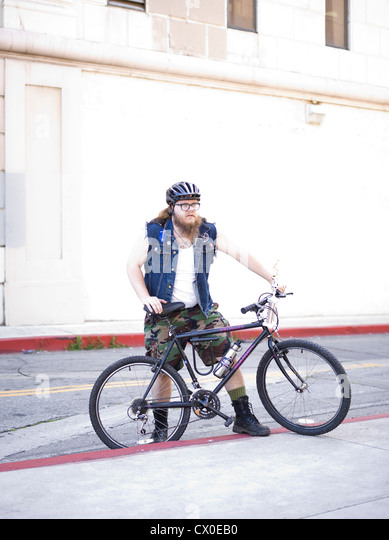 Man with Bicycle in City Street - Stock Image