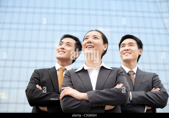 Business team standing in front of a tall building - Stock Image