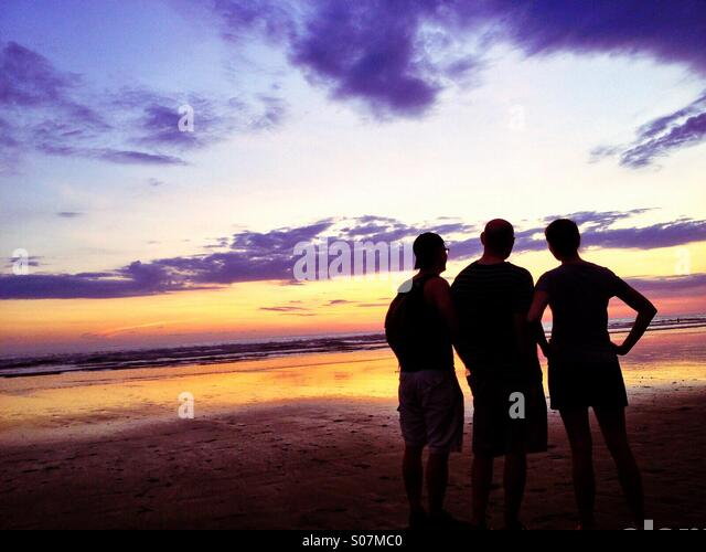 Three friends on the beach, Pacific Ocean, Costa Rica - Stock Image
