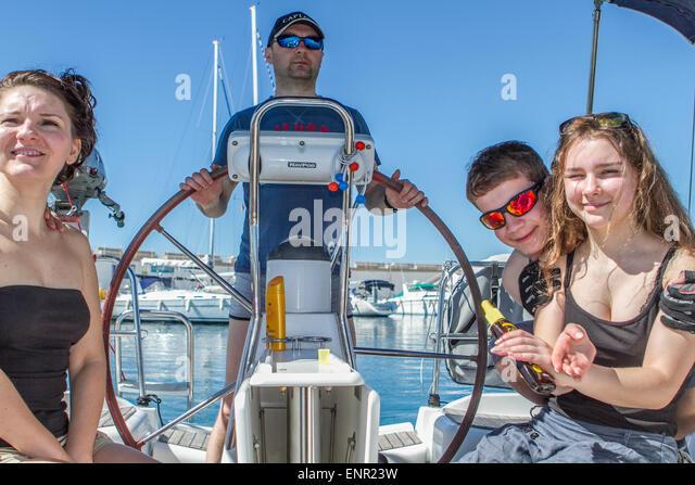 Family sailing, seating on a sail boat at the bay of Porto Colon, Travel to Majorka - Stock Image
