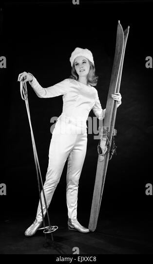 Woman in ski outfit with skis and poles. c.1964 - Stock Image