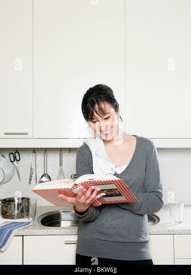 Woman with cookbook - Stock-Bilder