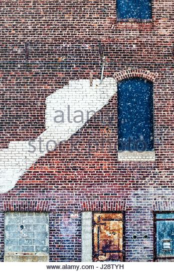 Urban brick building wall in the snow - Stock Image