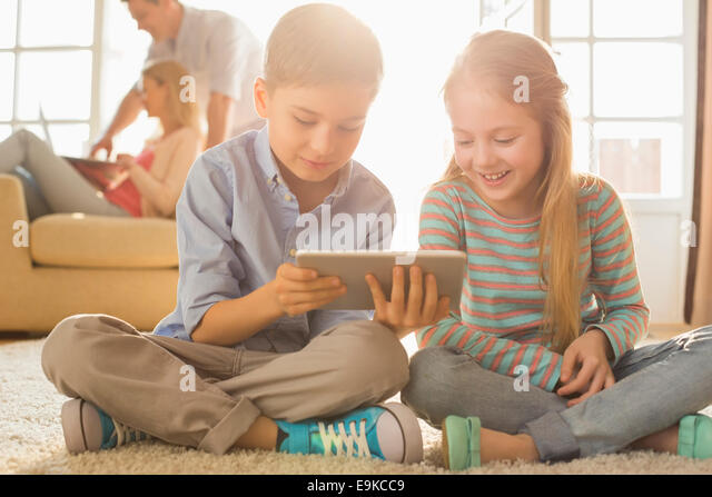 Happy siblings using digital tablet on floor with parents in background - Stock-Bilder