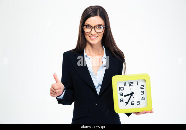 Smiling businesswoman holding clock and showing thumb up isolated on a white background - Stock Image