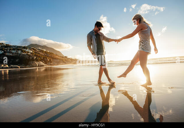 Beautiful young couple holding hands and playing on the shore. Happy young romantic couple in love having fun on - Stock Image