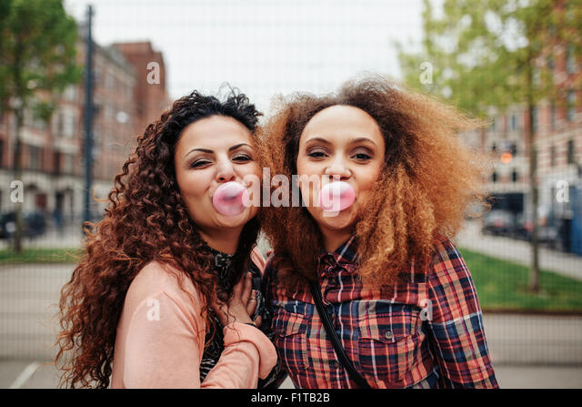 Happy young women blowing bubble gum. Best friends chewing bubble gum, outdoors. - Stock Image