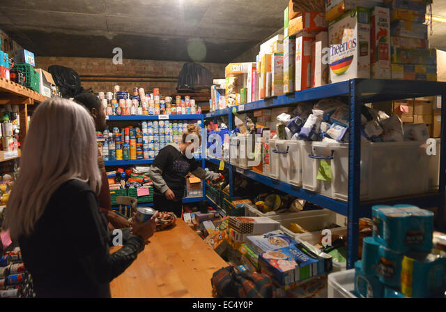 St Mary's Mission, Lambeth Road, London, UK. 9th December 2014. Volunteers working in the Foodbank. Food stored - Stock Image