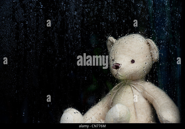 Sad Teddy bear looking through a window covered in rain drops - Stock Image