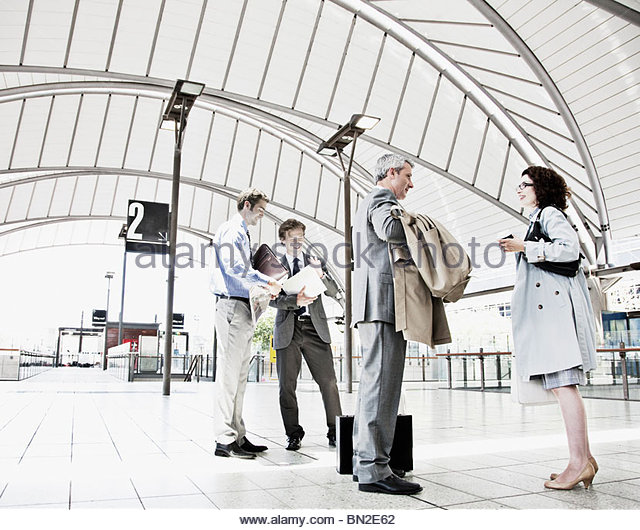 Business people waiting in train station - Stock Image