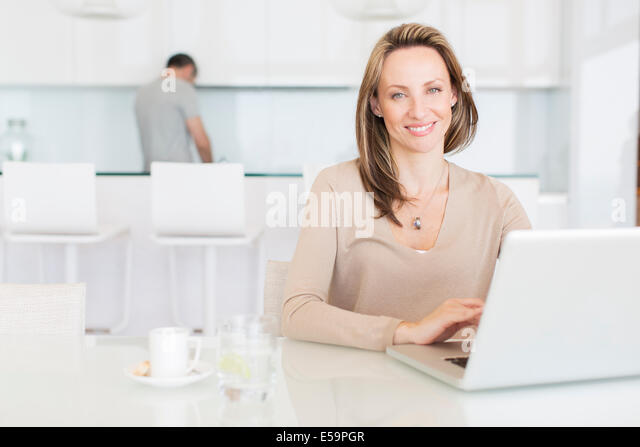 Woman using laptop at breakfast table - Stock Image