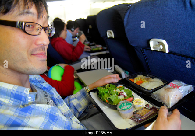 Chicago Illinois O'Hare International Airport ORD onboard United commercial airliner cabin Asian man passenger - Stock Image