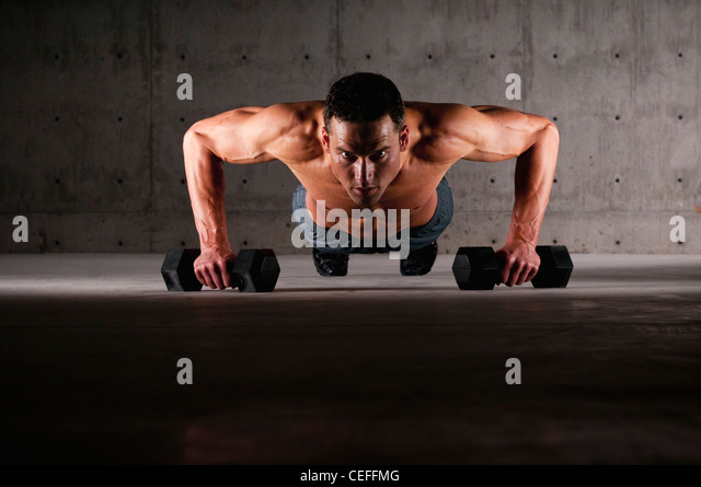 Athlete doing push ups on weights - Stock Image
