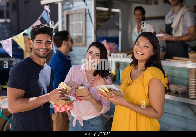 Portrait of friends standing with snacks in food truck van - Stock Image
