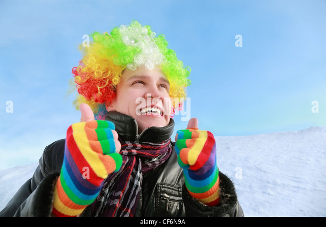 Man in wig and gloves of clown looks in sky and shows gestures hands - Stock Image