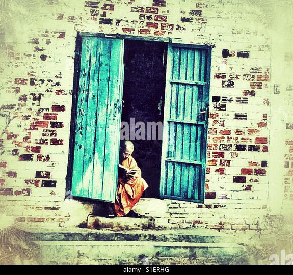 Monk reading in doorway - Stock-Bilder