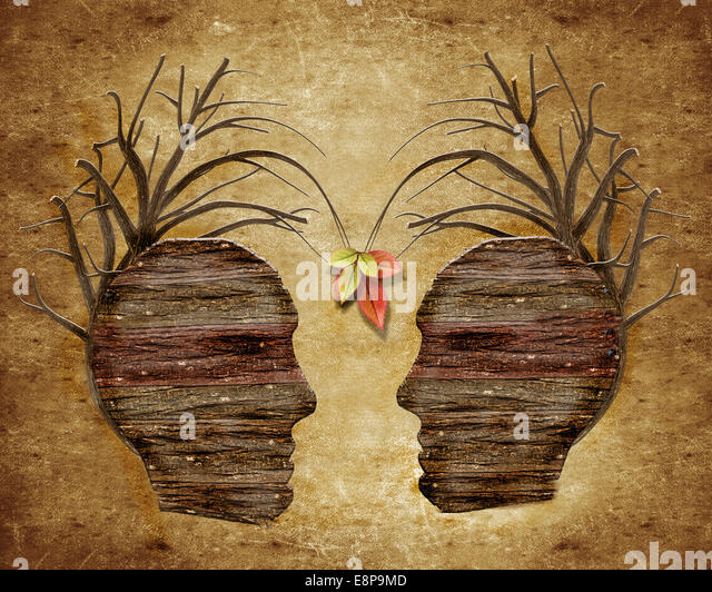 two wood human head and leaves - Stock Image