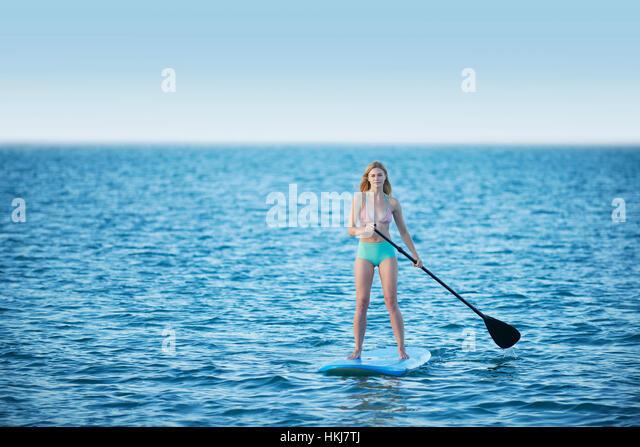 Young woman in bikini paddleboarding on summer ocean - Stock-Bilder