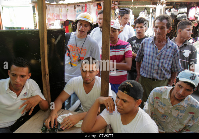 Nicaragua Granada Calle Atravesada shopping market watching soccer match football Hispanic man young mature group - Stock Image