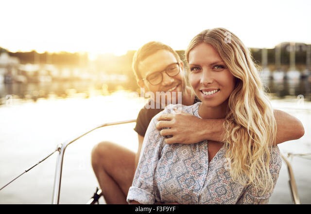 Young Couple In Love Sitting Outside on a Warm Summer Day - Stock Image
