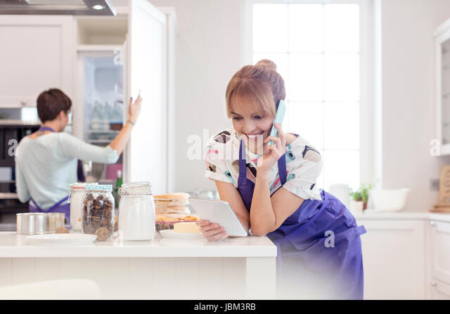 Female caterers baking and working in kitchen, talking on cell phone and using digital tablet - Stock-Bilder