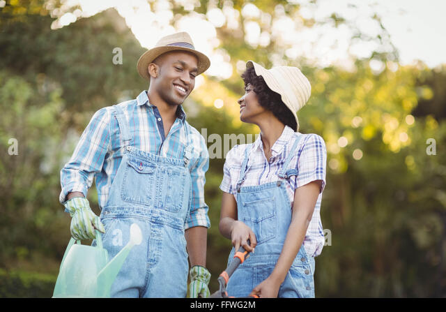 Smiling couple holding watering can and gardening shears - Stock Image