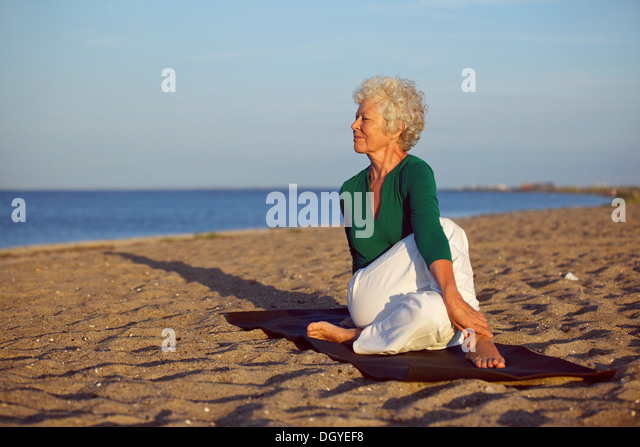 Senior woman performing a yoga routine on the beach. Elder woman doing stretching exercise on sandy beach with lots - Stock Image