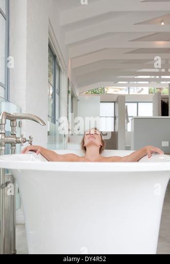 Woman Relaxing in Bathtub - Stock Image