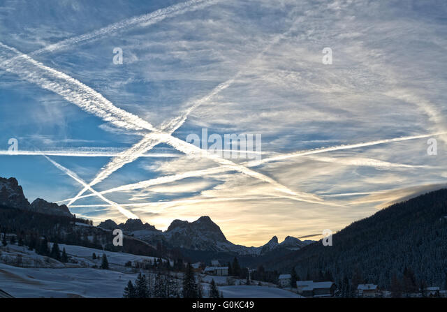 beautiful winter sunrise in the italian mountains and cloudy sky with aircraft contrails, Dolomiti - Stock Image