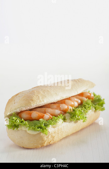 Baguette roll filled with prawns against white background. - Stock-Bilder