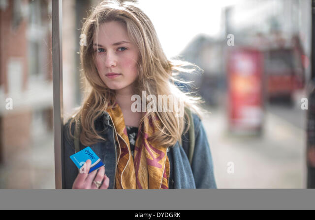 A young woman holds an Oyster card at a London bus stop. - Stock Image