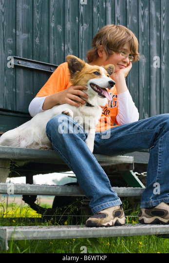 Boy sitting on a step with his dog - Stock Image