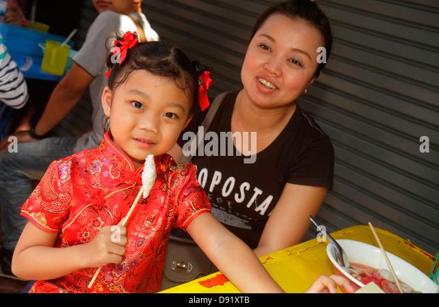 Thailand Bangkok Samphanthawong Chinatown Mangkon shopping market marketplace Asian girl daughter woman mother eating - Stock Image