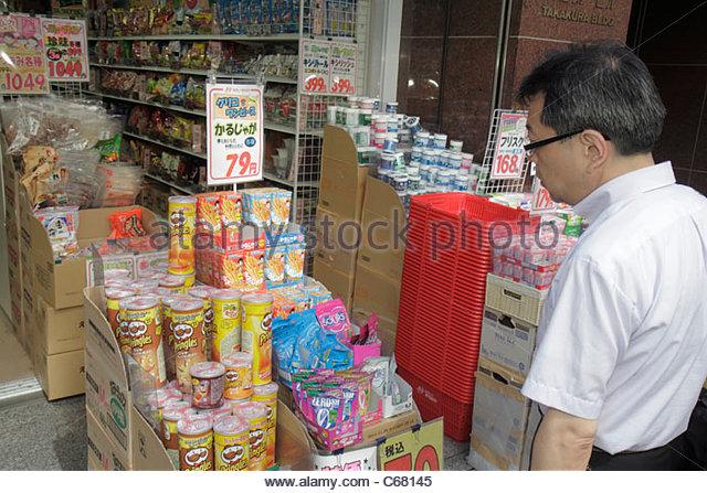 Tokyo Japan Shinjuku drugstore pharmacy kanji hiragana katakana characters Japanese and English for sale retail - Stock Image