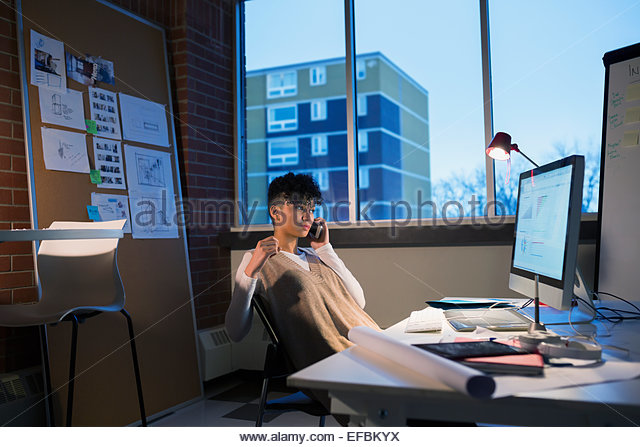 Graphic designer working late at computer in office - Stock-Bilder