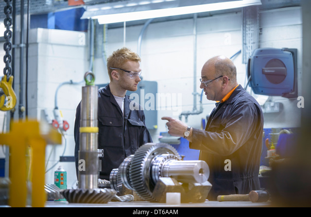 Engineer instructing apprentice at workstation in factory - Stock-Bilder