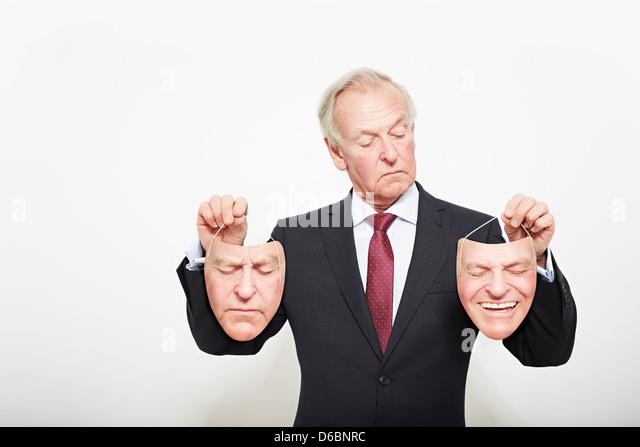 Businessman holding masks - Stock Image