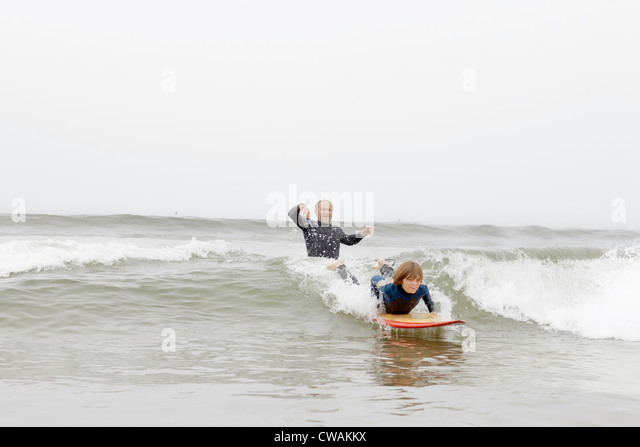 Surfing teacher and student in the sea - Stock Image