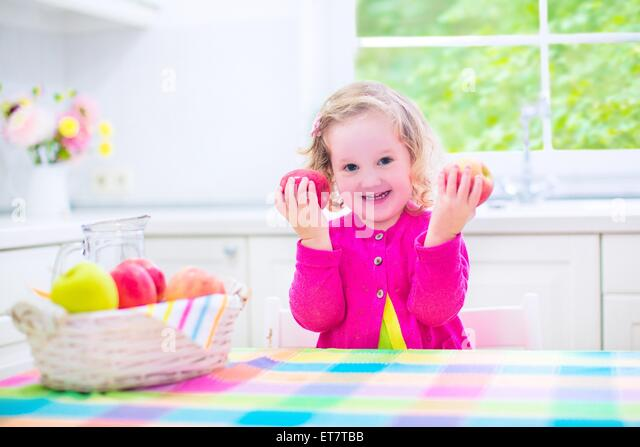 Funny happy laughing child, adorable toddler girl with curly hair wearing a pink shirt, eating red and green apples - Stock Image