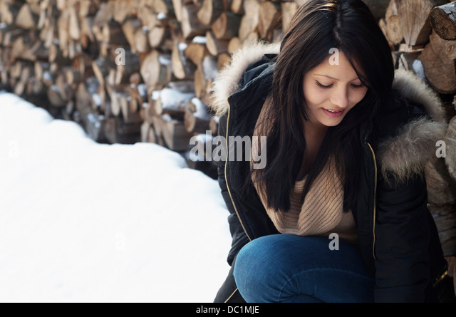 Candid portrait of young female in front of log pile - Stock Image