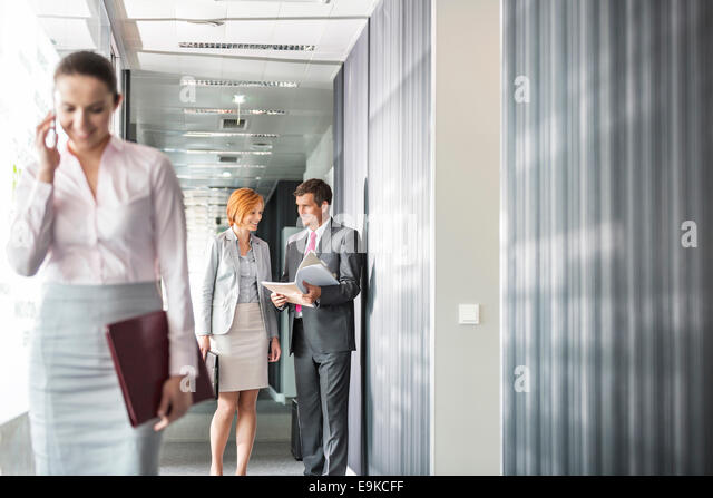 Business people discussing in corridor with colleague using cell phone in foreground - Stock-Bilder